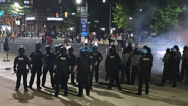 An Erie police SWAT team moves a crowd of demonstrators north on State Street between North Park Row and South Park in Erie during rioting on May 30. Police continue to investigate whether outsiders might have played a role in the riots.