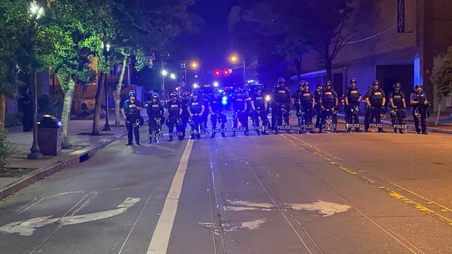 Police in riot gear have formed a line on Chestnut Street in downtown Wilmington as the 9 p.m. curfew goes into effect.