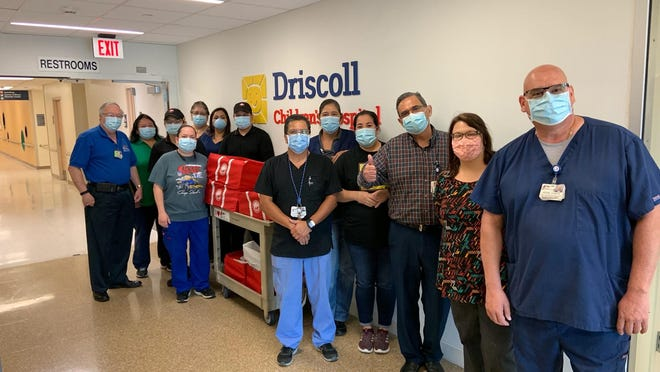 Richard Harris, Children's Miracle Network (CMN) Hospitals Administrator, Driscoll Children's Hospital (left), and members of Driscoll Children's Hospital Materials Management Department accept the donated meals from Fernando Cardenas and Juan Moreno with Panda Express.