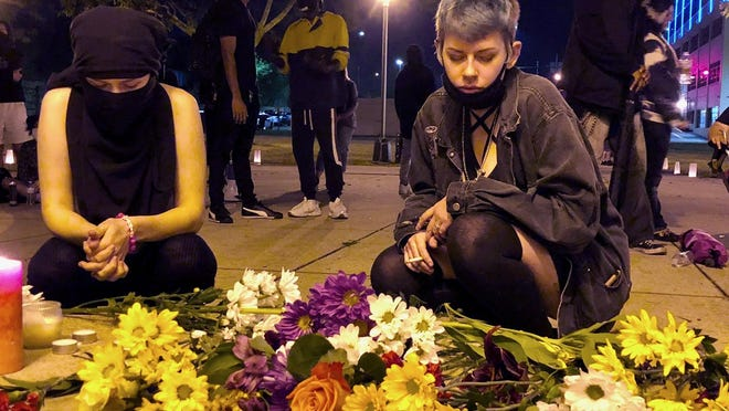 Two activists place flowers at the base of a gazebo during a candlelight vigil Monday at Davis Park in Rockford.