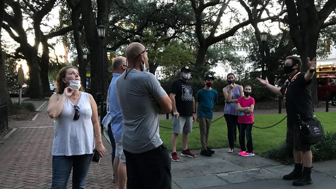 Jodie Thomas leads a Savannah Supernatural Tours group around some of the city's more haunted spots. Thomas said that he usually keeps his groups to around 20 people maximum and they abide by the coronavirus precautions issued by the city.