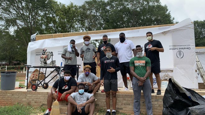 Wearing masks for protection, Gardner-Webb football players take a picture after helping at a home construction site.