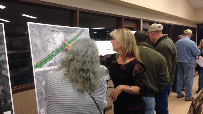 Kerry Oriol (right), a Providence project manager on the La. 28 East widening project, points to a map that shows where a roundabout might be placed at the highway's intersection with La. Highway 1207 Thursday night before a meeting at Buckeye High School.