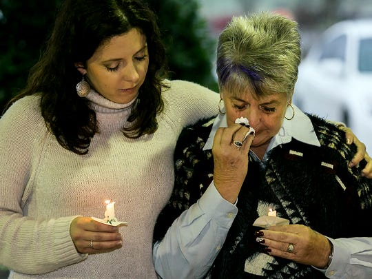 Suzanne Videon, right, mother of missing teen China Videon, and China's sister, Cheyann Videon, bow their heads during a prayer at Monday's candlelight vigil at Barfield Crescent Park.