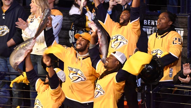 The Titans defensive backs wave towels and catfish before game 5 of the first round NHL Stanley Cup Playoffs at the Bridgestone Arena Friday, April 20, 2018, in Nashville, Tenn.