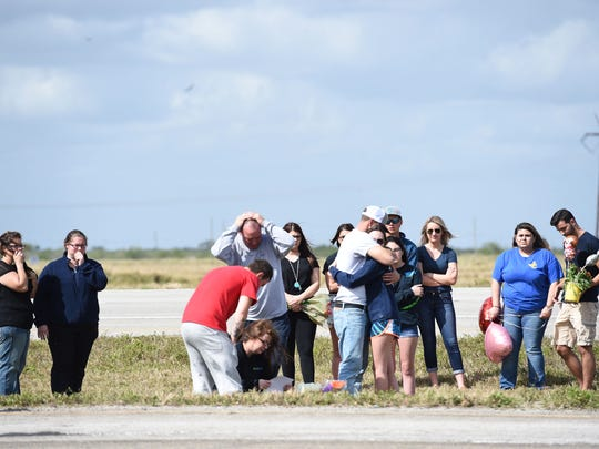 People gather Wednesday, Feb. 7, 2018, at the site of the fatal car crash on Okeechobee Road in western St. Lucie County that killed two teens, Santia Myriah Feketa, 18, of Fort Pierce, and Britney Lee Poindexter, 17, of Port St. Lucie.