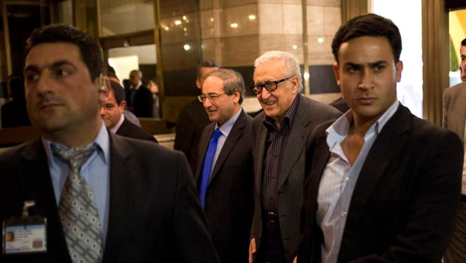 U.N.-Arab League envoy Lakhdar Brahimi, center right, and Deputy Syrian Foreign Minister Faisal Mekdad arrive to a hotel surrounded by security Monday.