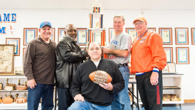Coaches and members of the 1975 Millville football team, Ed Andrews, Ron Lamb, Jim McCormick and Rich Andres, and Tony Surace pose for a photo with the 1975 state title trophy at the Millville Thunderbolt Club on Monday, November 28.