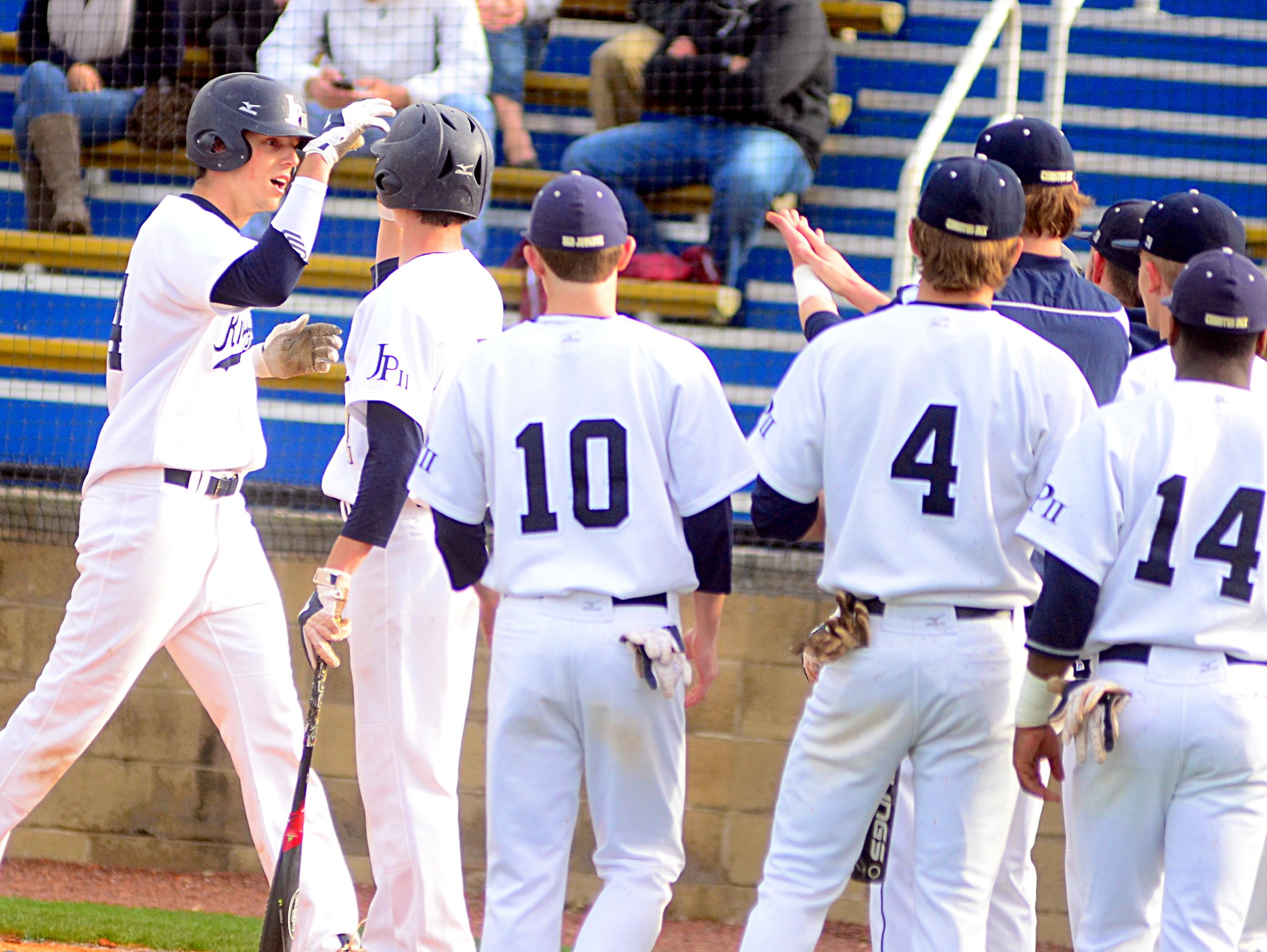 Pope John Paul II High senior Ryan Hatten (left) is greeted by teammates after his first-inning home run during game one of Friday evening's doubleheader. Hatten had two hits and drove in three runs.