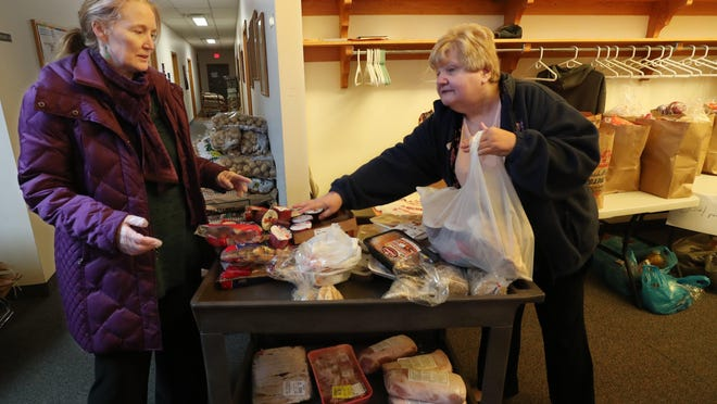 Bethany McKenney talks with Dorothy Somerville, executive director of Barberton Area Community Ministries, as Sommerville packs a bag of food March 24.
