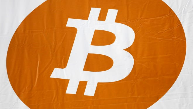 A bitcoin logo displayed at the Inside Bitcoins conference and trade show, Mon., April 7, 2014 in New York.