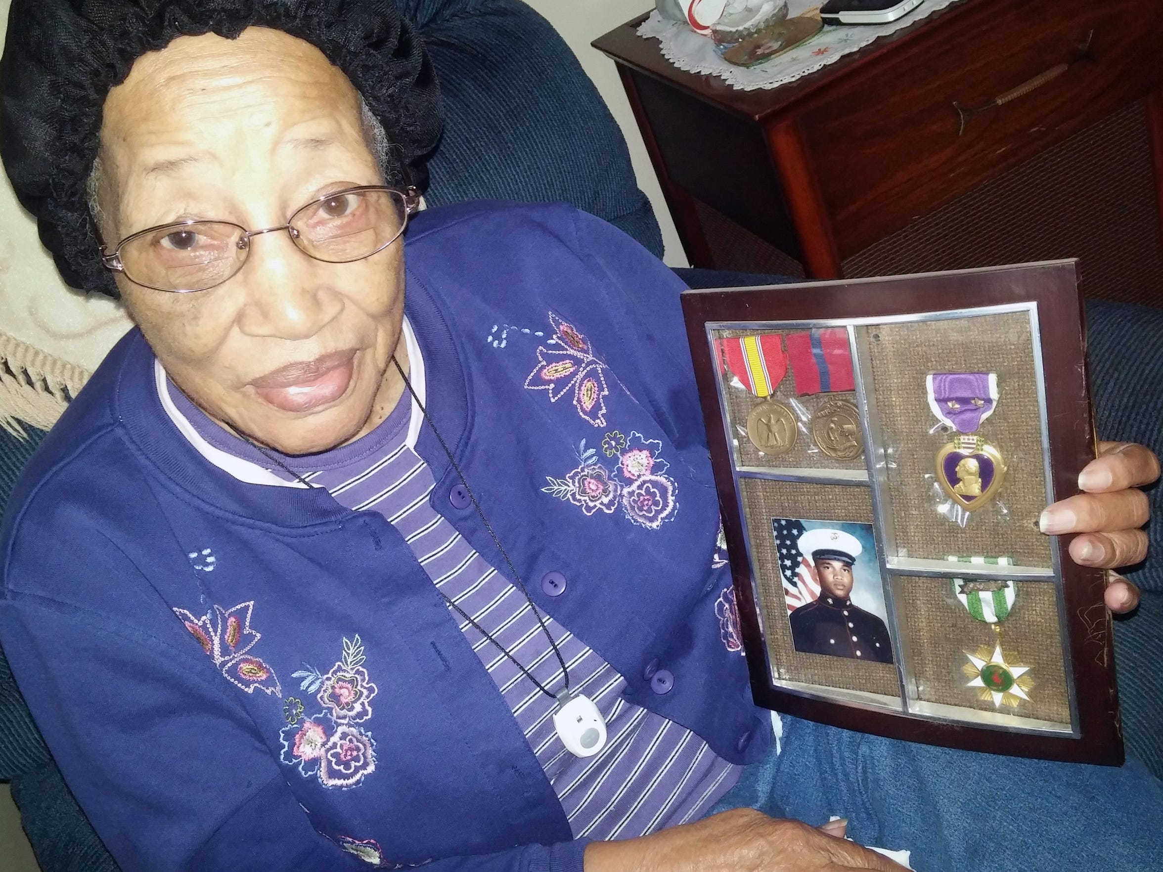 Arizona White of Staunton cradles the frame holding a photograph and the medals from her son Lin Williams who was killed in Vietnam.