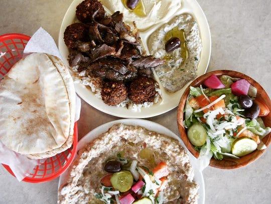 Clockwise from top: A lamb shawarma platter, salad,