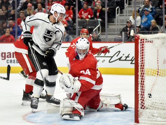 Los Angeles Kings center Anze Kopitar, left, of Slovenia, scores a goal past Detroit Red Wings goaltender Eric Comrie in the second period of an NHL hockey game Sunday, Dec. 15, 2019, in Detroit. (AP Photo/Jose Juarez)