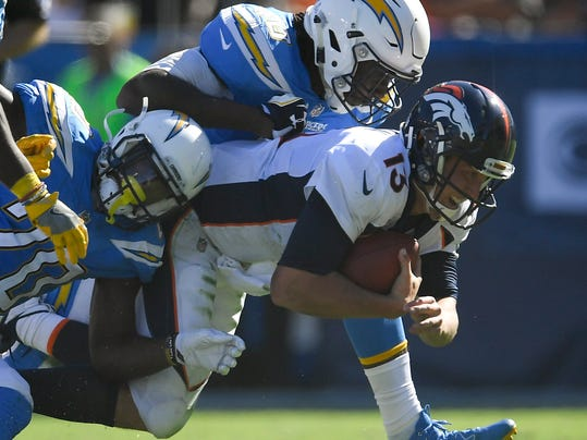 """FILE - In this Oct. 22, 2017, file photo, Denver Broncos quarterback Trevor Siemian, right, is tackled by Los Angeles Chargers defensive end Chris McCain, top and defensive back Desmond King during the first half of an NFL football game, in Carson, Calif. The Denver Broncos are red-faced over their poor play and their quarterback has a black and blue nose courtesy of his latest trouncing. It's only a bruise, Siemian said, but """"I probably should have broken it. I deserve it the way I played.""""(AP Photo/Mark J. Terrill, File)"""