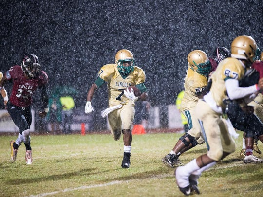 Lincoln running back Ricky Henrilus carries for a large