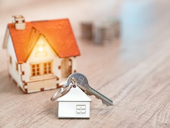 House key on a house shaped keychain resting on wooden