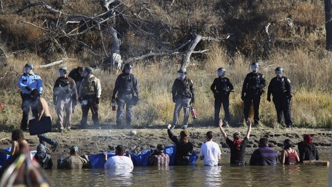 Protesters demonstrating against the expansion of the Dakota Access Pipeline wade in cold creek waters confronting local police Nov. 2, 2016 as remnants of pepper spray waft over the crowd near Cannon Ball, North Dakota.