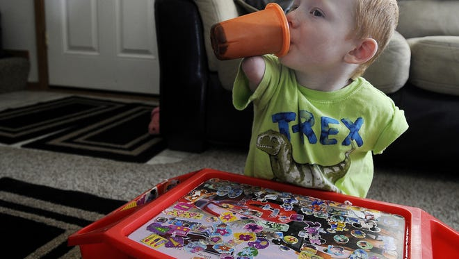 Austin Schoppert, 4, balances a sippy cup on his arm to drink.