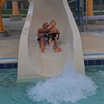Trent Tishkowski and his son Charlie use the slide at Chimney Park Pool in Windsor in this file photo