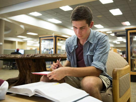 Freshman Nathan Christensen sits inside Zuhl Library on Aug. 17, 2016, finishing up his calculus 2 homework.