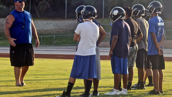 A group of Cathedral City High School players receive instructions during a practice session at the Lions' training field on Aug. 14. 2015.