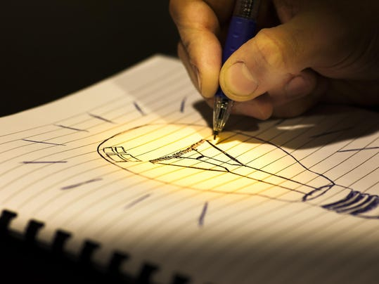 Hand draws light bulb with blue ink in copybook