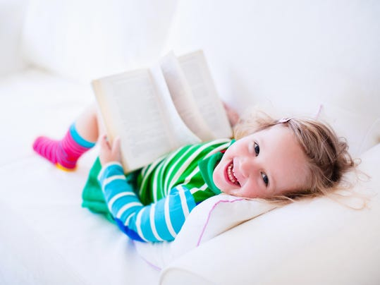 Beautiful little girl reading a book on a white couch