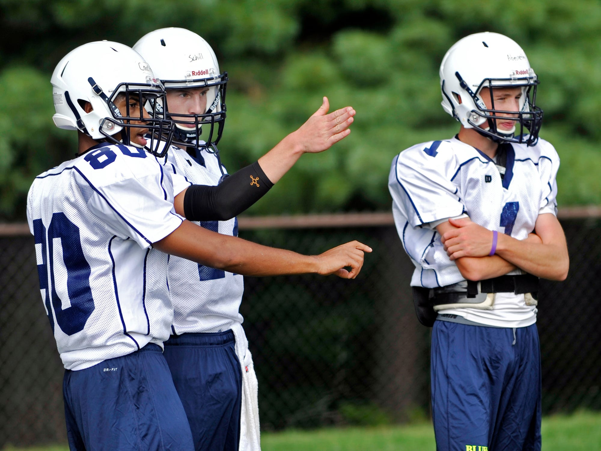 Asheville School's Mo Carlton, left, confers with his quarterback, David Schill, over a play during Tuesday's football practice.