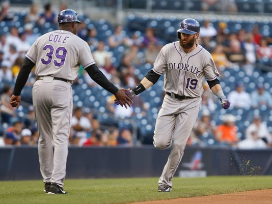 Colorado Rockies' Charlie Blackmon is congratulated by third base coach Stu Cole after his leadoff home run against the San Diego Padres in the first inning of a baseball game Wednesday, Sept. 24, 2014, in San Diego.  (AP Photo/Lenny Ignelzi)