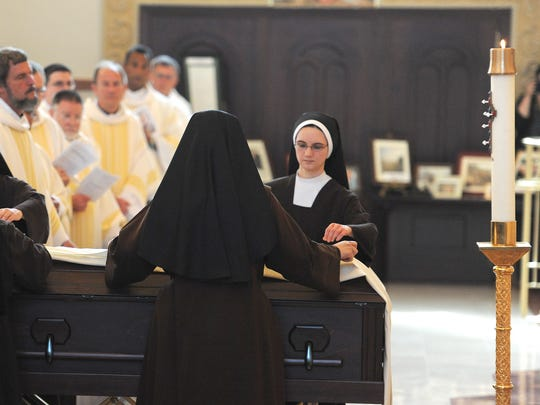 The Carmelite Sisters of the Devine Heart of Jesus place the pall over the casket of Most Rev. John Jeremiah McRaith at the start of the funeral service on Friday at St. Stephen Cathedral.