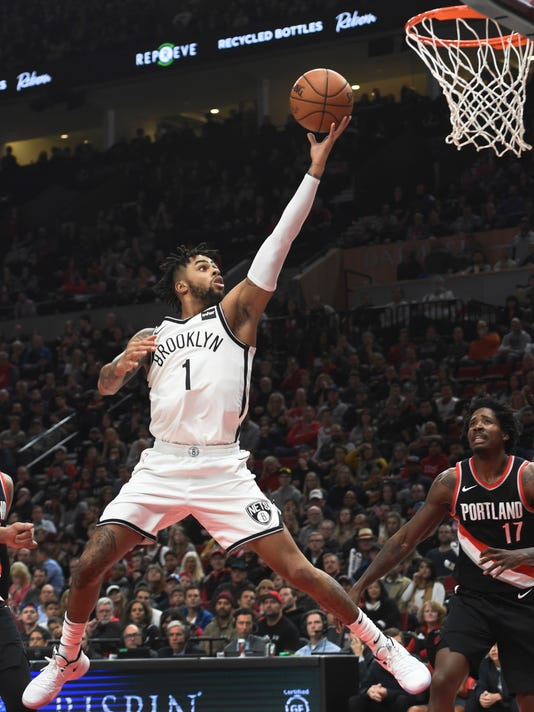 Brooklyn Nets guard D'Angelo Russell drives to the basket on Portland Trail Blazers forward Ed Davis during the second half of an NBA basketball game in Portland, Ore., Friday, Nov. 10, 2017. The Nets won 101-97. (AP Photo/Steve Dykes)