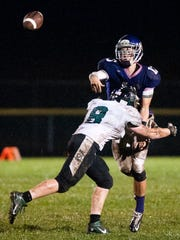 Millersport quarterback Jonah Butts gets a pass away before being driven to the ground by a Fisher Catholic defender on Friday night.