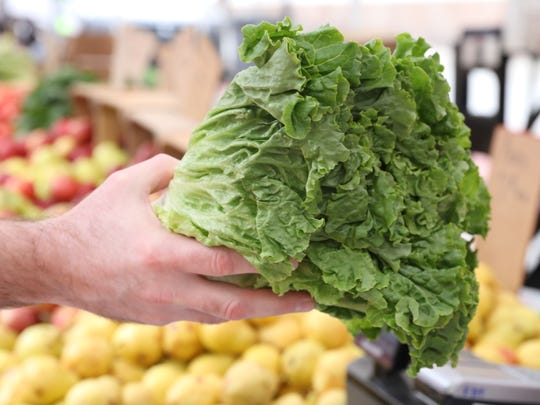 A customer buys green leaf lettuce from Rolling Ridge Farms, which is located in Mifflinburg, PA, at the White Plains farmers market May 16, 2018.