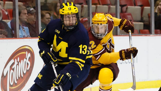 Michigan's Zach Werenski (13) skates with the puck against Minnesota on March 21, 2015, in Detroit.