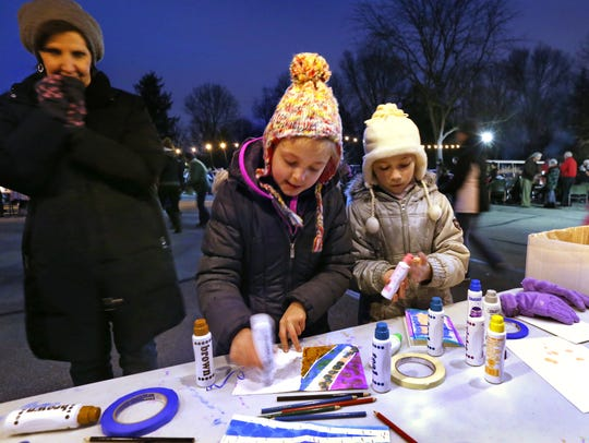 Kali Chamberlain, center, and Katelyn Bray, right, paint colorful cards, one of the activities at the 2014 Winter Solstice event at the Indianapolis Museum of Art, as Kali's mother Kristi Chamberlain, left, watches.