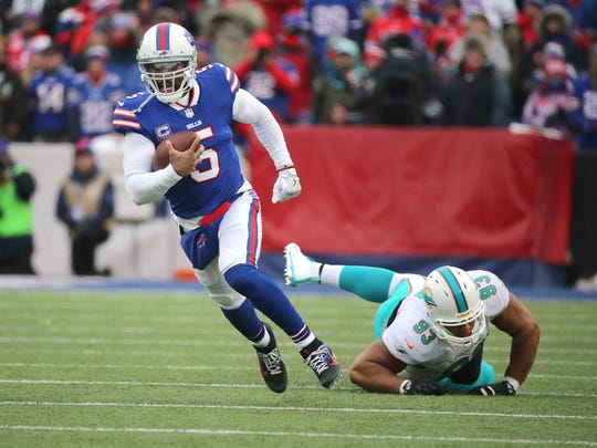 Bills quarterback Tyrod Taylor escapes pressure from Dolphins Ndamukong Suh.