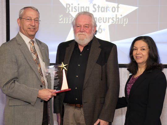 Chris Bouchard (left), state director of the Missouri Small Business & Technology Development Centers, presents the Rising Star of Entrepreneurship award to Lynn Reeves (center), owner of Lew's Fishing Tackle.  Also pictured is Isabel Eisenhauer, assistant director of the Missouri State University Small Business & Technology Development Center consultant who assisted Lew's.