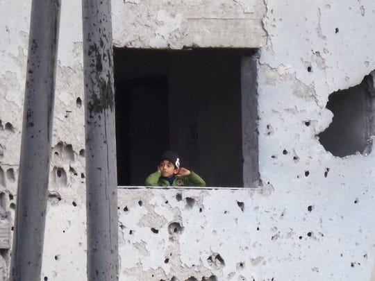 A Syrian boy looks out from a window inside the bullet-riddled