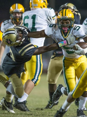 Raymond Calais Jr. (5) of Cecilia with the stiff arm on the Jackets defense on night Oct. 23, 2015.