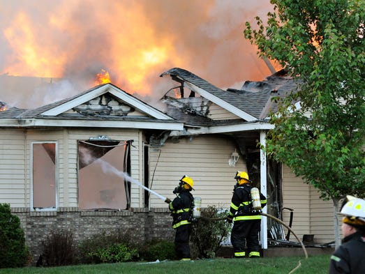 Firefighters from area departments battle the flames after a small plane crashed into a home at 731 Garden Place in Sauk Rapids Friday.