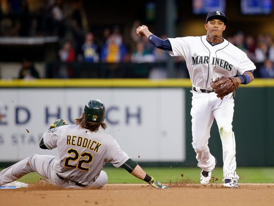 Seattle Mariners shortstop Ketel Marte, right, throws to first after forcing out Oakland Athletics' Josh Reddick at second base in the first inning in a baseball game Friday, April 8, 2016, in Seattle. Marte completed the double play on Danny Valencia at first. (AP Photo/Elaine Thompson)