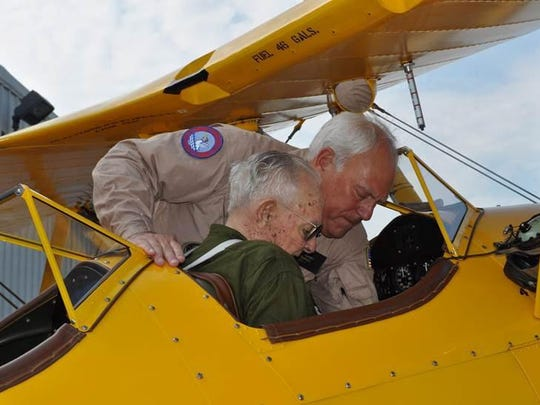 Veteran Navy pilot B.T. Smith gets strapped into the front cockpit of Roy Kinsey's N2S-4 Navy Stearman before the 2014 Pensacola Beach Airshow.