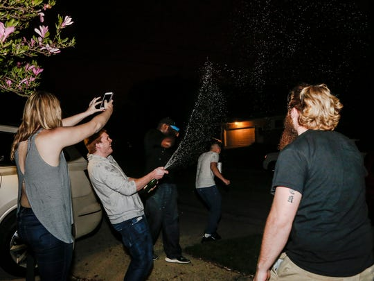 Former Western Michigan University football standout, Okemos native Taylor Moton celebrates with friends, and gets doused with champagne Friday evening, April 28, 2017, after the NFL draft watch party at his parents' home in Okemos.  Moton was the final pick in the second round of the 2017 NFL draft and will play for the Carolina Panthers.