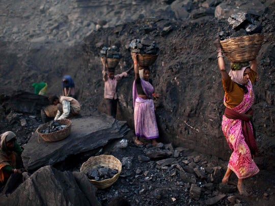 People carry baskets of coal scavenged illegally at