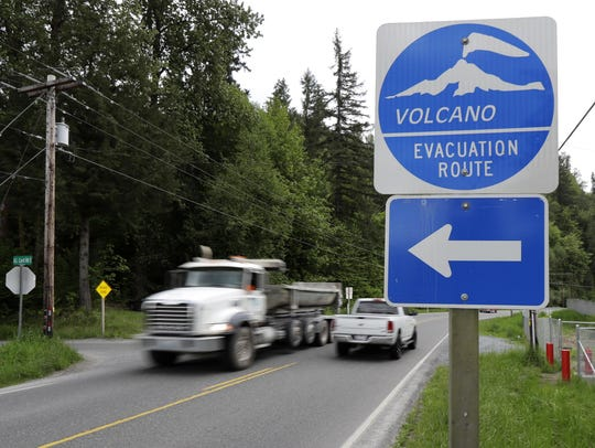 A volcano evacuation route sign directs traffic and