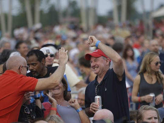 Fans high five each other while Doobie Brothers performed at Red White and Blue Ash at Summit Park in 2015