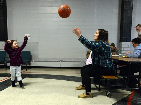 Volunteer Grace Romine, 16, tosses a basketball with her sister Bella Romine, 3, Tuesday, Jan. 2, 2018, at Connexion West in Lancaster. Connexion West has been opened as a warming center since last week.