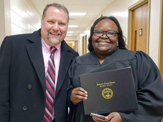 With Robertson County Director of Schools Chris Causey at her side, Springfield's Latasha Cross shows off the high school diploma she earned after a 16-year struggle with math.