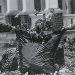 Caleb Carter, left, and Emily Kelley, right, hold a lawn and leaf bag open while Gracin Dorsey slam dunks an armful of leaves in November of 1990.